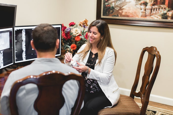 Dr. Priscilla Jelsing explaining dental implants to a male patients with computer technology