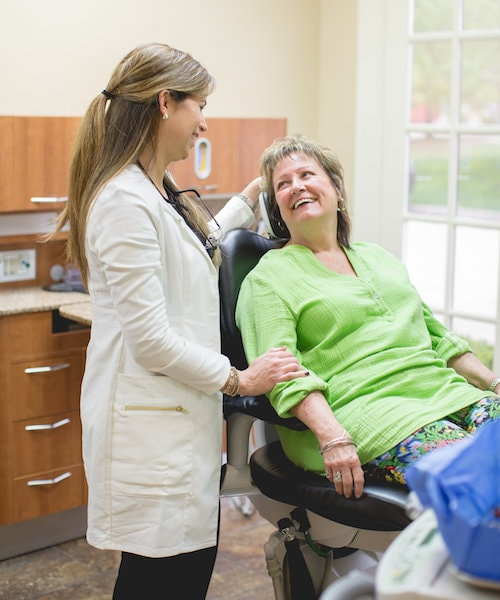 Dr. Jelsing discussing dental crowns with a female patient sat in the dentist chair