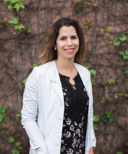 Dr. Priscilla Jelsing stood in front of a natural-looking background wearing her white coat