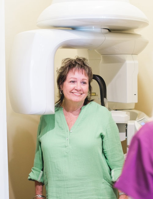 Female patient smiling while she stands in the CBCT scanner
