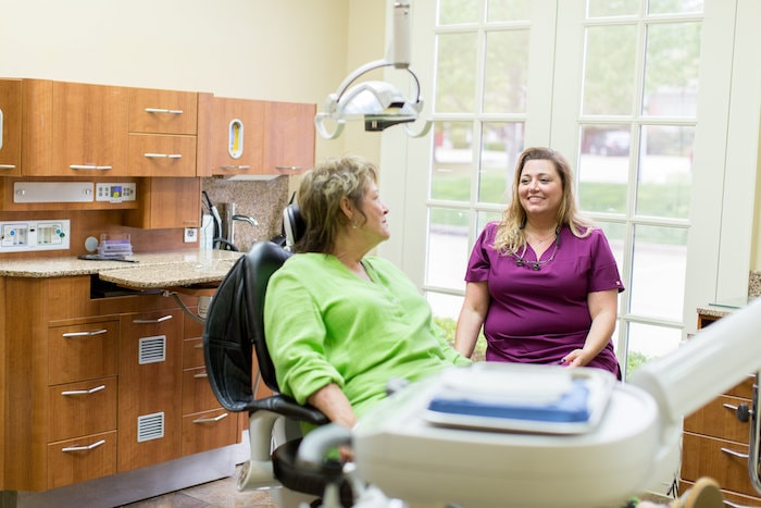 One of our team members caring for a female patient while she sits in the dentist chair