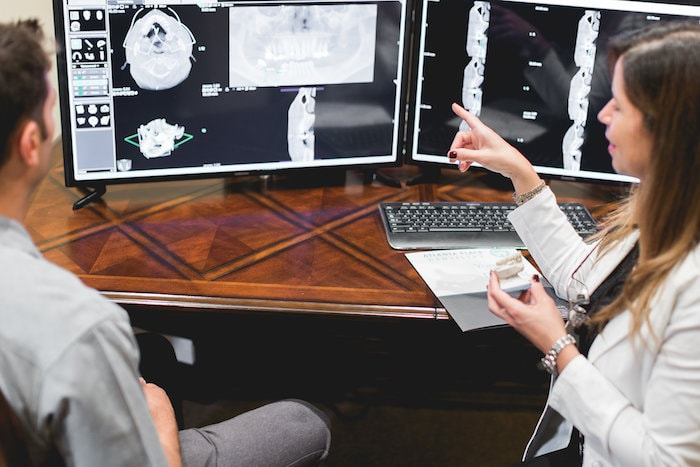 Dr. Jelsing using computer technology and digital x-rays to talk to a male patient about tooth extractions