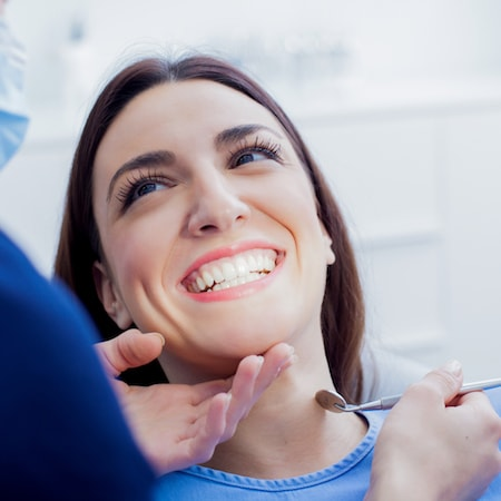 Woman sitting in the dentist chair and looking up and smiling at Dr. Jelsing