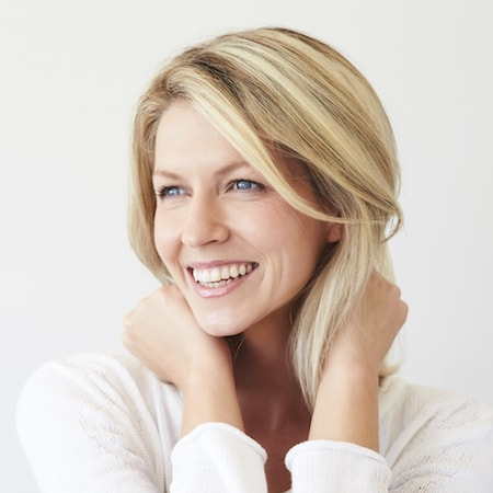Blonde woman smiling while holding the back of her neck