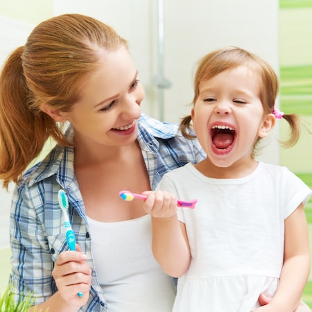 Mother with her very young daughter. The daughter is holding her toothbrush and has her mouth open very wide.