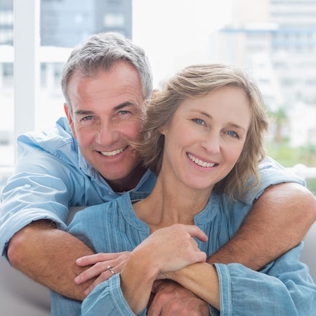 Older lady smiling while sitting and her husband is hugging her over the shoulder and also smiling