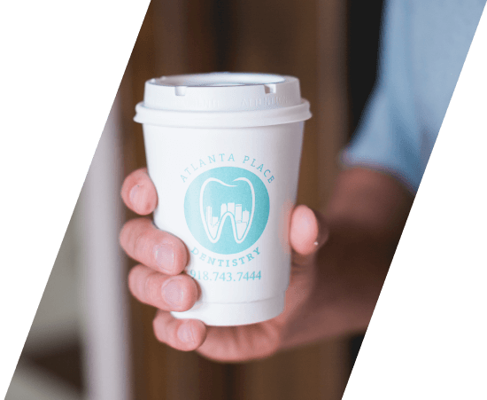 Shot of a hand holding a cup with Atlanta Place Dentistry Logo