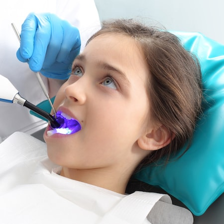 Teenage girl sitting in the dentist chair with a dental laser shining on her tooth