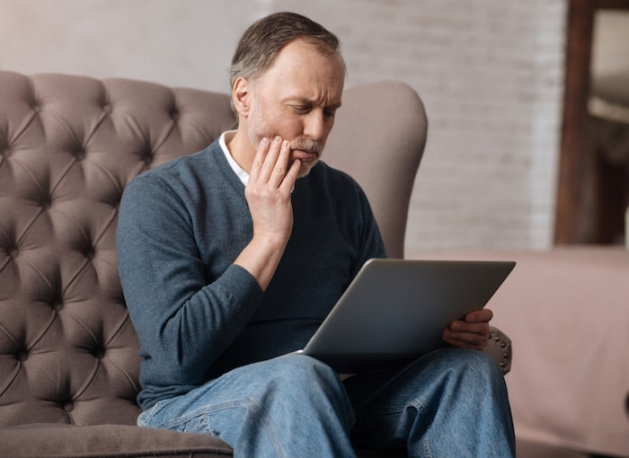Man holding his jaw as he has TMJ pain and looking at his laptop to book his appointment at Atlanta Place Dentistry