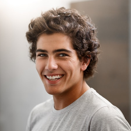 Young man with curly hair and a grey t-shirt, standing side-on and smiling