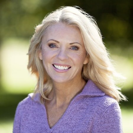 Older lady with very white teeth smiling and wearing a purple top
