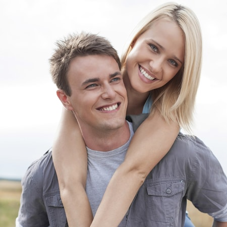 Blonde lady smiling on her male partner's back as she shows off her healthy gums