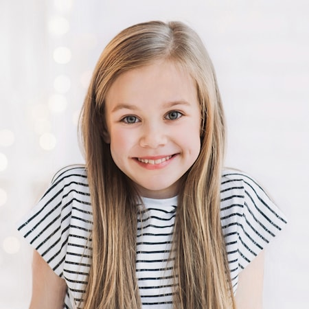 Little girl with long hair and a stripy top smiling after her sealants treatment