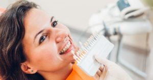 woman smiling, dentist holding up teeth whitening samples